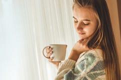 舒适家 有杯子的妇女由窗口的热的饮料 看窗口和饮料茶 早晨好用茶 放松的女孩 库存照片