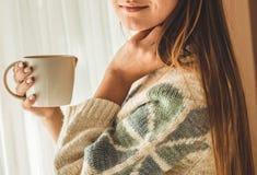 舒适家 有杯子的妇女由窗口的热的饮料 看窗口和饮料茶 早晨好用茶 放松的女孩 免版税库存图片