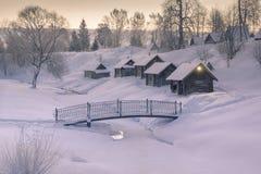 舒适小的房子在冬天村庄的小山早晨在冻河附近的 免版税库存照片