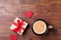 舒适早餐为情人节 咖啡、礼物或者当前箱子和红色心脏在土气木台式视图 库存图片