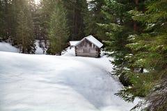 舒适木客舱在多雪的森林里 免版税库存图片
