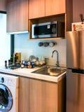 舒适木层压制品的小厨房在一个现代顶楼 库存图片