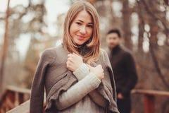 舒适温暖羊毛衫走的少妇室外在秋天森林里,有背景的男朋友的 免版税库存图片