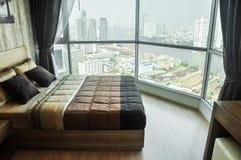 舒适现代卧室内部有在背景的城市视图 库存照片