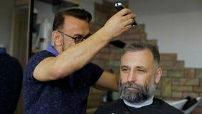 舒适理发店,参与专家美发师理发人年迈 在客户的椅子的一个可敬的商人 股票视频