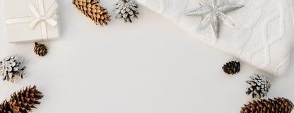 舒适白色圣诞节快乐构成 被编织的冬天手套、袜子、毛线衣在锥体旁边,新年装饰和礼物 flatley 顶层 免版税库存图片