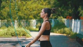 舒适的体育成套装备跳绳的年轻运动员妇女在一个运动场在公园 影视素材