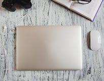 舒适的工作地点特写镜头顶视图在接近的膝上型计算机、照片照相机、牛奶店和玻璃办公室 库存照片