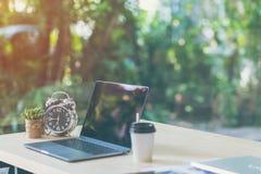 舒适的工作场所、办公桌有黑屏膝上型计算机的和时钟,植物,自然轻的bokeh背景 免版税库存图片