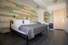 舒适的床在时髦的卧室在旅馆里 免版税库存照片