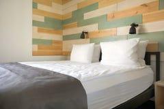 舒适的床在时髦的卧室 免版税库存照片