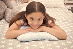 舒适的枕头 女孩微笑的愉快的孩子在与特征模式枕头和逗人喜爱的格子花呢披肩的床放置在她的卧室 库存图片