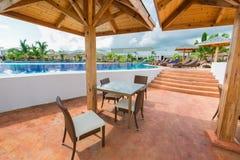 舒适的游泳池和酒吧就座区域美好的邀请的看法与放松的人,游泳在背景中 库存图片