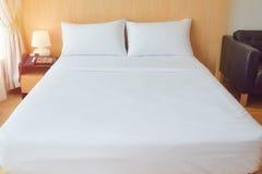 舒适的白色床在舒适的家具的屋子里和衣裳提供 库存照片