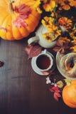 舒适秋天早餐平的位置在桌上的在乡间别墅里 热的茶、南瓜、百吉卷和花 库存照片
