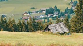 舒适非常老葡萄酒木房子在小山的奥地利阿尔卑斯与在背景的绿草新现代 股票录像