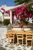 舒适餐馆在Chora街道的开花的树下在米科诺斯岛,基克拉泽斯海岛 希腊 免版税图库摄影