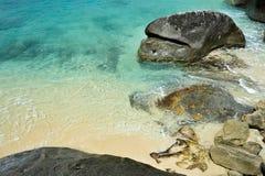 舔一个多岩石的海滩的美丽的清楚的蓝色海 免版税库存图片