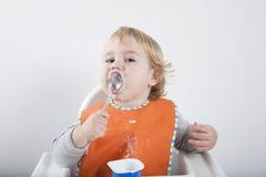 舔匙子的婴孩 免版税库存图片