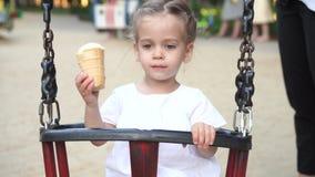舔在奶蛋烘饼锥体的女孩冰淇淋夏令时在有美好的日落的公园 股票视频