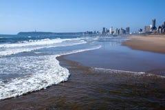 舔在德班海滩前面的波浪岸 库存图片