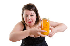 舔她的嘴唇和注视一个瓶子桃子的妇女 图库摄影