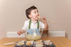 舔木匙子的年轻男孩 图库摄影