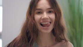 舔舌头的画象微笑的妇女对白色牙前面镜子在卫生间里 影视素材