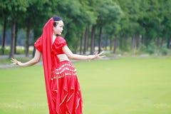 舞蹈亚裔中国肚皮舞表演者的亮光红色礼服的 图库摄影