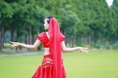 舞蹈亚裔中国肚皮舞表演者的亮光红色礼服的 免版税库存照片