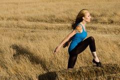 舞蹈姿势的妇女在草的域 免版税库存照片