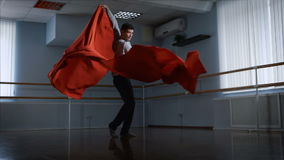 舞蹈家执行他的情感舞蹈使用一块大红色布料在一个大演播室 现代舞的属性 优美 股票录像
