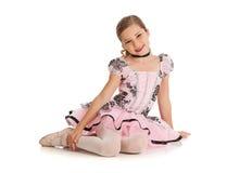 舞蹈家:逗人喜爱的跳芭蕾舞者坐地板 库存图片