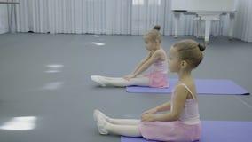 舞蹈服装的两个小女孩是坐和做锻炼 股票录像