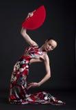 舞蹈演员摆在红色妇女的风扇佛拉明&# 库存照片