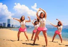 舞蹈的啦啦队员摆在手在头顶上在海滩反对海 库存图片