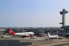 航空交通管制塔和终端4有维尔京的大西洋波音747和加勒比航空公司波音737在门在JFK 库存照片
