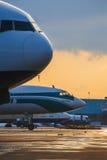 航空器停车处在日落的机场 免版税库存照片