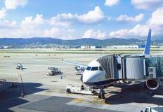 航空器在有多云天空的机场飞行 免版税库存照片