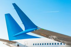 航空器` s尾巴和机体的小翅膀翼反对蓝天与飞机在飞行水平面上 库存照片