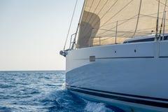 航行与被卷扬的前桅前方的帆的游艇弓 免版税库存图片