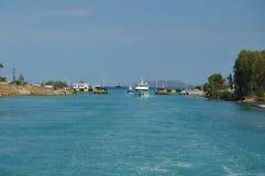 航行在他们束缚,但是科林斯运河的入口的小船不混合爱琴海和Gree蓝色颜色靛蓝  库存图片