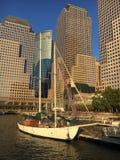 航行在天空线曼哈顿,纽约前面的船 图库摄影