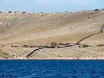 航行在沿一个海岛村庄的一条游艇在克罗地亚,单独种田在一个空的荒岛上,科纳提群岛国家公园 库存图片