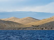 航行在沿岩石和波浪荒岛风景的一条游艇在科纳提群岛国家公园在夏天克罗地亚,地中海 免版税库存照片
