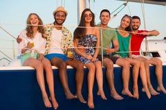 航行在游艇的愉快的青年人 库存照片