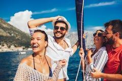 航行在游艇-假期、旅行、海、友谊和人概念的朋友 库存照片