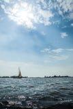 航行在湖的船有云彩和太阳的与海岛 免版税库存照片