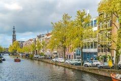 航行在通过Westertoren的Prinsengracht的一条运河船的游人 免版税库存图片