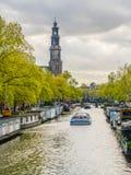 航行在通过Westertoren的Prinsengracht的一条运河船的游人 免版税库存照片